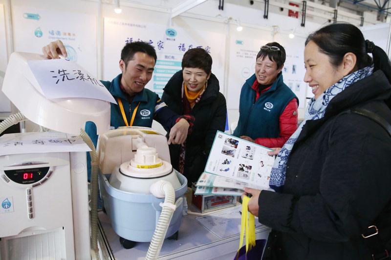 11月29日,工作人员(左一)在北京国际老龄产业博览会上介绍洗澡机。