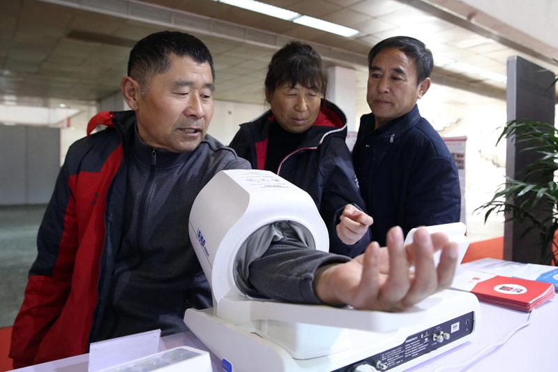 11月29日,参观者在北京国际老龄产业博览会上体验测血压。