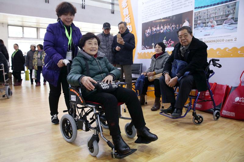 11月29日, 参观者(前右)在北京国际老龄产业博览会上体验可折叠的轻便小巧型电动轮椅。